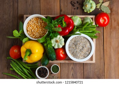 Health food with high fibre. Dietting, whole wheat cerals, grains, vegetables, antioxidants and vitamins: zzuchini, tomatoes cucumbers beans Wooden background