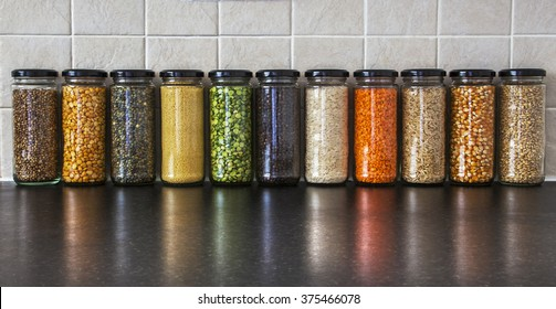 Health Food ingredients - choice of herbs, seeds and pulses in spice jars, with reflections - lentils, split peas, pearl barley, coriander seed, black pepper, cous cous, corn, and rice - panorama.