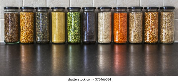 Health Food Ingredients -  herbs, seeds and pulses in spice jars, with reflections - lentils, split peas, pearl barley, coriander seed, black pepper, cous cous, corn, and rice - panorama.
