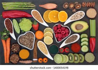 Health food selection for liver detox concept with fresh fruit, vegetables, legumes, herbal medicine, grains, seeds, supplement powders, herbs and spices. Top view on slate.