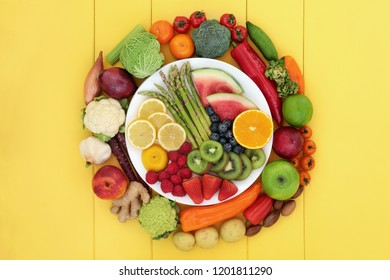 Health food for vegans with fresh fruit and vegetables, herbs, spices and nuts on and surrounding a porcelain plate. High in antioxidants, dietary fibre, vitamins and omega 3. Top view on yellow wood