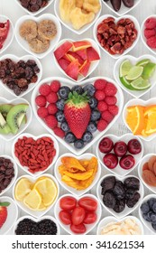 Health and fruit superfood selection in heart shaped porcelain dishes on a wooden distressed background. High in vitamins and antioxidants.