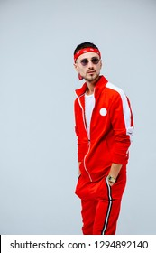 health, fun, people sport concept - happy young man wearing red sport suit on white background.