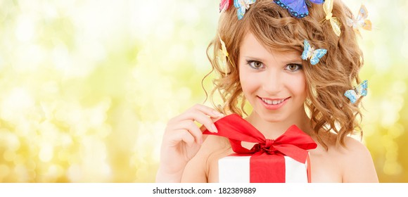health, holidays and beauty concept - happy teenage girl with butterflies in hair opening gift box
