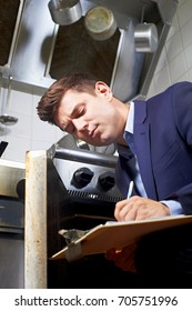 Health Inspector Looking At Oven In Commercial Kitchen