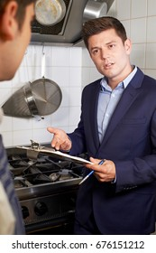 Health Inspector Meeting With Chef In Restaurant Kitchen