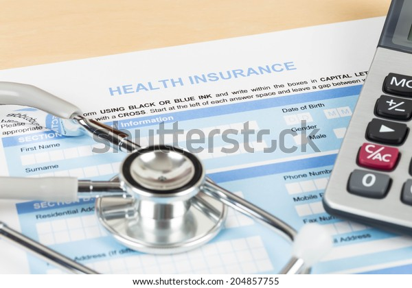Health insurance application form with calculator and stethoscope concept for life planning