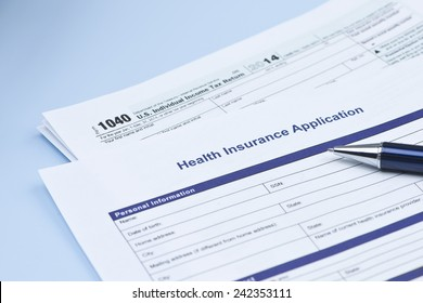 Health insurance application with United States 1040 tax form and pen.