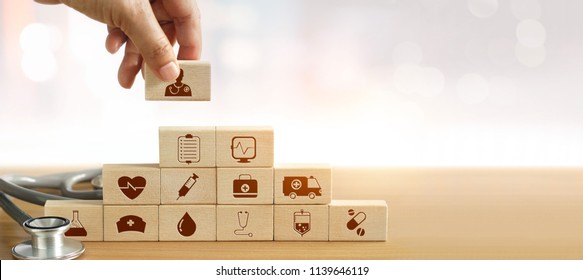 Health Insurance concept, Hand of medicine doctor holding wood block and stacking with icon healthcare medical and stethoscope on background.