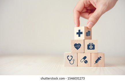 Health Insurance Concept, Reduce Medical Expenses, Hand flip wood cube with icon healthcare medical and coin on wood background, copy space.