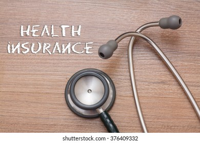 Health insurance concept : stethoscope on note book with wood background