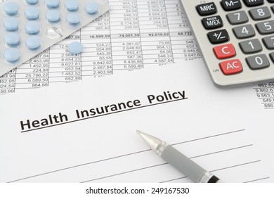 health insurance policy with calculator and pen