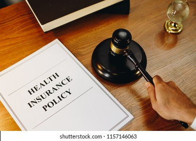 Health insurance policy documents with gavel at the side