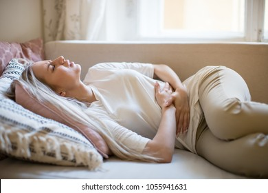 Health issues problems concept/Young Caucasian woman suffering from stomach pain, feeling abdominal pain or cramps, lying on sofa, indoors/Period menstruation, women health problem, food poisoning/