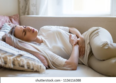 Health issues problems.Young Caucasian woman suffering from stomach pain, feeling abdominal pain or cramps, lying on sofa.Period menstruation, female health problem, aching belly and gynecology