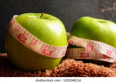 HEALTH LIFESTYLE CONCEPT: Green apples and measuring tape over black rustic background. Selective focus.