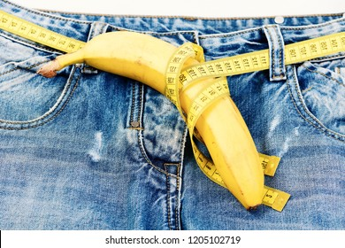 Health and male sexuality concept. Pants with banana imitating male genitals, selective focus. Kinky fruit on jeans crotch, wrapped with measure tape, close up. Measure tape instead of jeans belt.