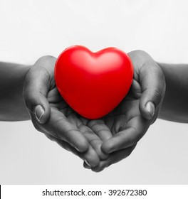 health, medicine and charity concept - close up of african american female hands with small red heart