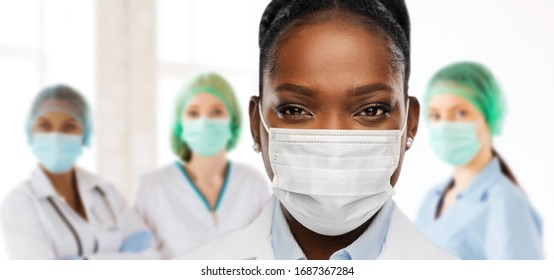health, medicine and pandemic concept - close up of african american female doctor or scientist in protective mask over medical workers at hospital on background
