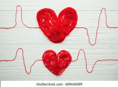 Health, medicine, people and cardiology concept. Abstract red hearts. Problems with heart. Hearts is made of red thread. Charity, health care, donation concept.