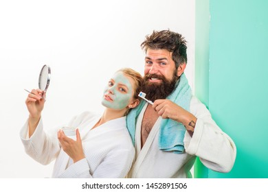 Health. Morning routine. Family life. Husband and wife. Morning procedures. Woman with cosmetic facial mask. Couple. Relationship. Morning treatments. Bearded man with with toothbrush cleaning teeth.