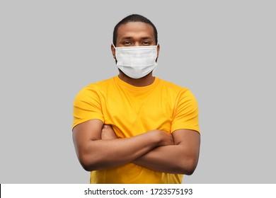concept de santé, de pandémie et de sécurité - jeune afro-américain portant un masque médical de protection contre les maladies virales sur fond gris