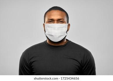 健康とパンデミック、安全のコンセプト – グレイの背景にウイルスの病気から保護するために、顔を保護する医療マスクを着用したアフリカ系の若い男性