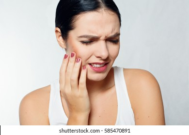 health, people, Dental and lifestyle concept - Teeth Problem. Woman Feeling Tooth Pain. Closeup Of Beautiful Sad Girl Suffering From Strong Tooth Pain. Attractive Female Feeling Painful Toothache