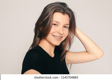 health, people, dentist and lifestyle concept - Portrait of teen girl showing dental braces. candid portrait of a girl wearing braces, with hair motion. laughing girl wearing braces, cheerful portrait