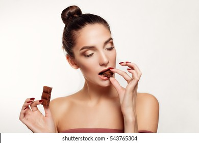 health, people, food and beauty concept - Lovely smiling teenage girl eating chocolate