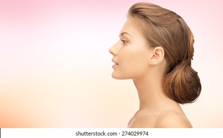 health, people, plastic surgery and beauty concept - beautiful young woman face over pink background