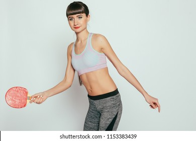 health, people, Sport and lifestyle concept - Young woman holding a table tennis racket and ball. Young happy fitness girl with sporty body at studio on a gray background.