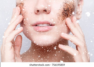 health, people, winter, christmas, and beauty concept - Smiling woman with short hair, bald cleans the skin coffee skrub, over snow, close-up portrait. Clean Fresh Skin close up. Spa Woman Smiling