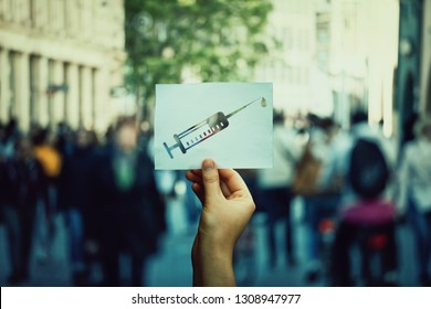 Health problem after vaccination process or junkie hand holding a paper sheet with syringe symbol, crowded street background. Drug addiction social issue concept. Narcotic substance human dependence.