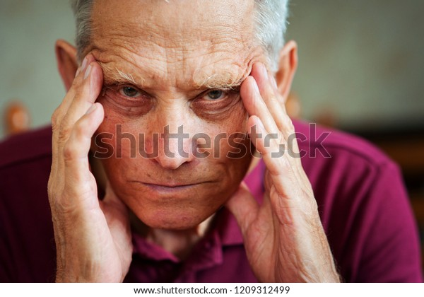Health problems in old age. Elderly man holds hands on his head.
