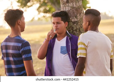 Health problems and social issues. Teenagers smoking electronic cigarette in park.