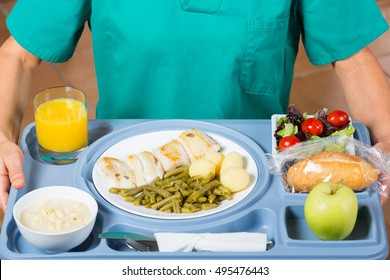 Health professional with a tray of food to a patient