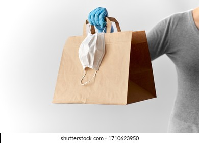 health protection, safe shopping and pandemic concept - close up of woman with paper bag, face protective medical mask and glove
