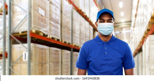 health protection, safety and pandemic concept - happy indian delivery man in blue uniform wearing face protective medical mask for protection from virus over warehouse background