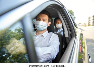 health protection, safety and pandemic concept - male taxi driver wearing face protective medical mask driving car with passenger