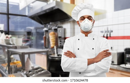 health protection, safety and pandemic concept - indian male chef cook wearing face protective mask or respirator with crossed arms over kebab shop kitchen background