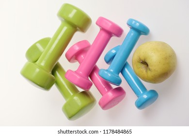 Health regime and fitness symbols. Dumbbells near green apple on white background. Healthy lifestyle and sports concept. Apple fruit and pink, green and blue barbells making pattern, top view