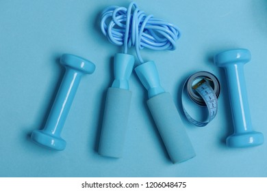 Health regime and fitness symbols. Dumbbells and skipping rope in cyan color on blue background, top view. Jump rope and barbells next to rolled measure tape. Fit shape and sport concept
