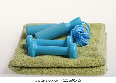 Health regime and fitness symbols. Dumbbells and skipping rope in cyan color on white background, close up. Jump rope and barbells placed on green towel. Healthy lifestyle and sports concept