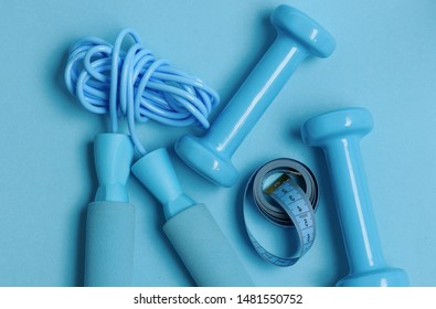 Health regime and fitness symbols. Fit shape and sport concept. Dumbbells and skipping rope in cyan color on blue background, top view. Jump rope and barbells next to rolled measure tape