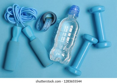 Health regime and fitness symbols. Jump rope, water bottle, measure tape and barbells, topview. Fit shape and sport concept. Bottle, tape roll, cyan dumbbells and skipping rope on blue background