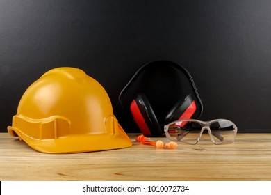 HEALTH AND SAFETY CONCEPT. Personal protective equipment on wooden table over black background.