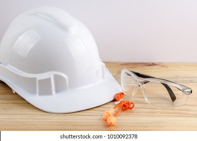 HEALTH AND SAFETY CONCEPT. Personal protective equipment on wooden table over white background.