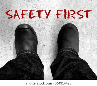 Health Safety and environment (HSE) copy space concept with a view of man wearing safety shoe and a safety slogan Safety First.
