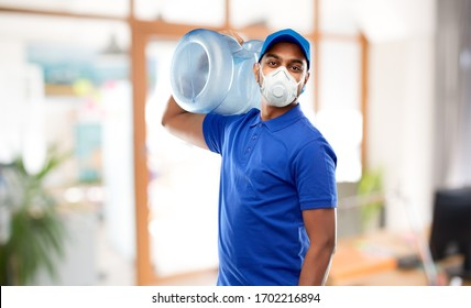 health, safety and pandemic concept - happy indian delivery man with water barrel wearing face protective mask or respirator for protection from virus disease over office background